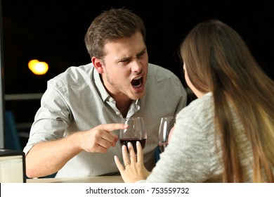 Angry couple arguing furiously in a bar at night