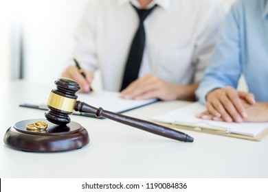 Angry couple arguing telling their problems to Judge gavel deciding on marriage to conclude an agreement on the divorce. They quarrel and argue with each other.