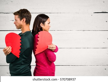 Angry couple holding broken heart against wooden background