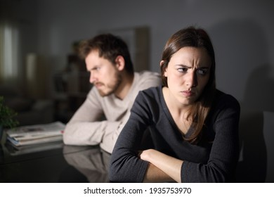 Angry couple ignoring each other sitting in the living room at home in the night