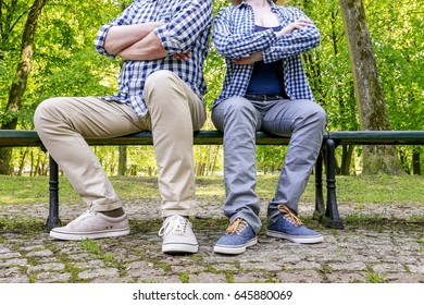 Angry couple sitting on the bench in beautiful summer park.