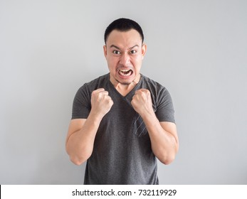 Angry and crazy asian man in black t-shirt and skinhead hair style.
