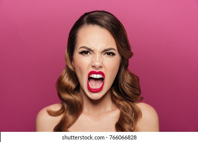 Angry crazy lady with styling and make up screaming isolated over pink