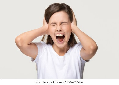 Angry crazy scared teen girl covering ears screaming feeling annoyed, stubborn stressed outraged young woman shouting in tantrum suffering from loud noise isolated on white grey studio background