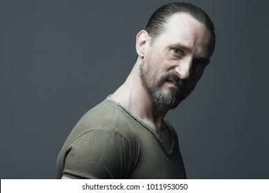 Angry criminal concept. Emotional portrait of 40-year-old strong brutal man over dark gray background. Hair brushed back. Rocker, biker style. Close up. Copy-space. Studio shot