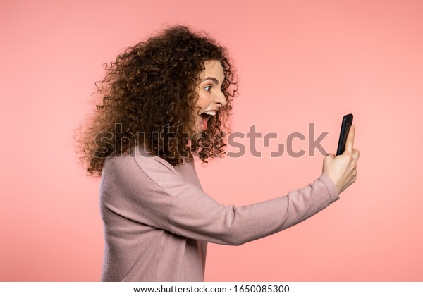 Angry curly woman screaming down, swears with somebody. Using mobile phone. Stressed and depressed girl on pink background.