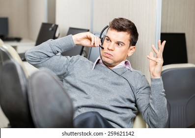 Angry customer service representative gesturing while using headset in office