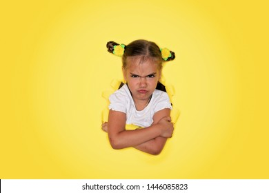 Angry cute 6-7 years old girl looking from the round shaped hole in the colored cardboard, empty space for advertising text in torn paper, background texture