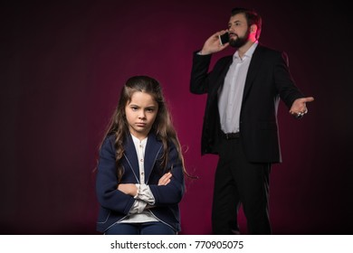 angry daughter standing with crossed hands while father talking by smartphone on burgundy
