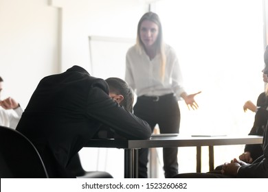 Angry disappointed female team leader boss looking at tired fallen asleep young male employee at business meeting. Unmotivated lazy worker feeling exhausted during stressful workday at office.