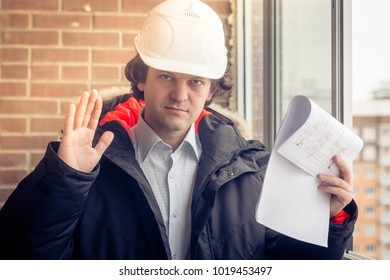 An angry disgruntled builder worker in a helmet with project drawings plans in his one hand and mobile phone in another hand screams on someone. Bad executed work. Aggressive man. Soft focus, toned.