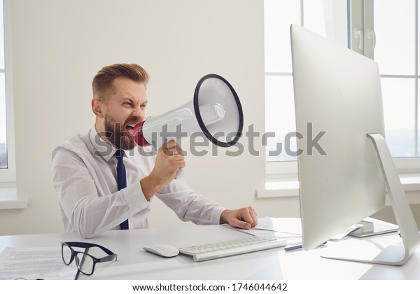 Angry displeased boss businessman shouting in megaphone into a computer
