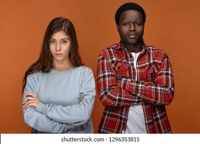 Angry displeased young African man and Caucasian woman being in bad mood, dissatisfied with their child, scolding him for misbehavior, crossing arms on chests, having irritated annoyed looks