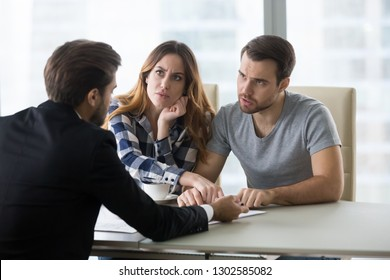 Angry dissatisfied couple arguing meeting lawyer or manager having legal fight complaints on bad client service, annoyed mad customers claiming change in contract terms demanding fraud compensation