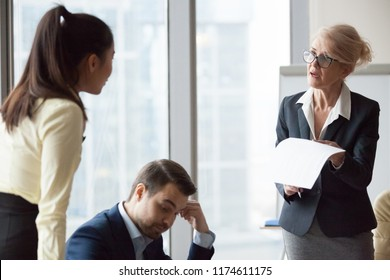 Angry dissatisfied director business woman criticizing work, financial report accusing asian woman and man worker. Subordinate feels guilty and frustrated. Conflict, problems mistakes, dismiss concept
