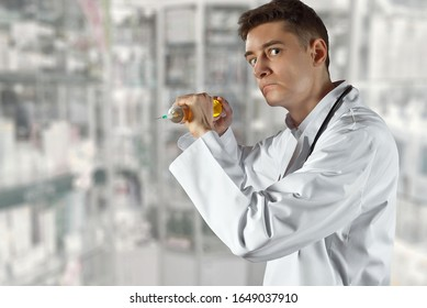 An angry doctor with a big syringe in his hands. Bad medic. Concept of young inexperienced doctor. Man in white coat on a background of shelves with medicines.