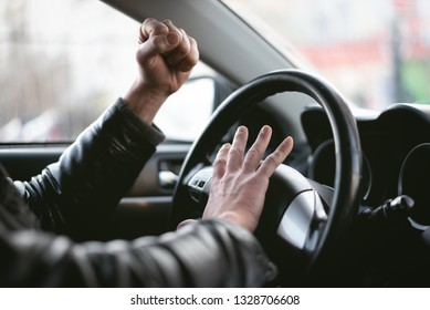 Angry driver is honking and is yelling by sitting of a steering wheel. Road aggression concept. Traffic jam.