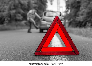 Angry driver kicking the tires on broken car and red warning trangle - black and white concept