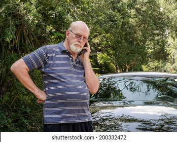 Angry elderly man on cell phone calls for roadside assistance for car malfunction or breakdown emergency.