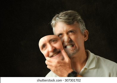 An angry, emotional, depressed, bipolar disorder man is revealing his true self as he takes off a fake smile happiness mask that looks exactly like his face.