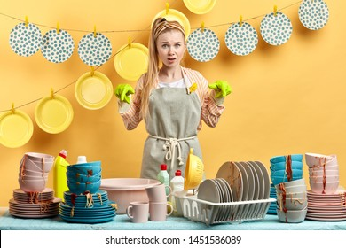 angry emotional frustrated sad housewife with pointing at dirty cutlery. Is t for me Are you joking Do I have to wash the dishes blonde girl with ponytail is scared of messy table