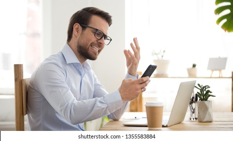 Angry employee annoyed by broken or discharged mobile phone, receiving bad news, furious businessman looking at smartphone screen, missed or unwanted call, problem with mobile device app