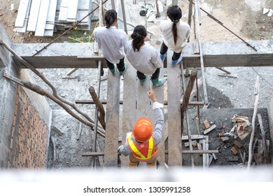 Angry engineer boss pointing finger threatens colleague at construction site. top view.