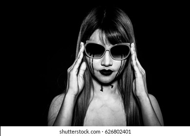 Angry enrage Asian woman in black and white isolated in black background. Portrait of beautiful Asian woman with black tears makeup for sadness, losing, anger, rage, breakup, killer concepts.