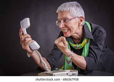 Angry, enraged senior woman yelling at a landline office phone,