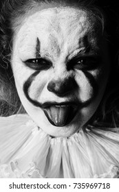 angry evil clown, show tongue looking at camera close up, monochrome