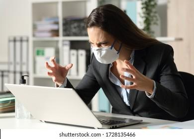 Mujer ejecutiva enojada mirando el portátil evitando el cóvid-19 sentado en su escritorio en la oficina por la noche