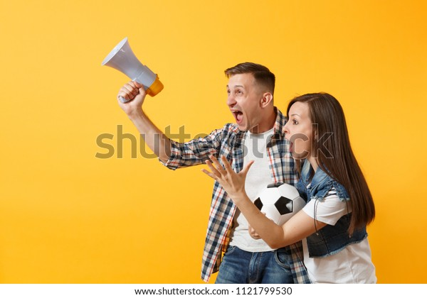 Angry expessive crazy couple, woman man football fans screaming, upset of loss, goal of favorite team with soccer ball, megaphone isolated on yellow background. Sport family leisure lifestyle concept