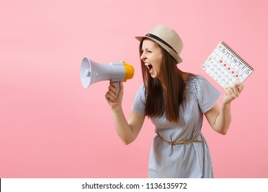 Angry expression wild woman screaming in megaphone, holding periods calendar for checking menstruation days isolated on pink background. Medical healthcare, pms mood gynecological concept. Copy space