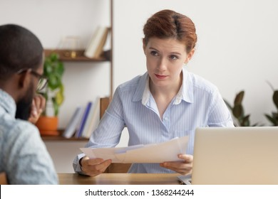 Angry female boss dissatisfied with bad financial result in report demand explanation from stressed incompetent african employee scolding upset intern for mistake in paperwork having conflict at work
