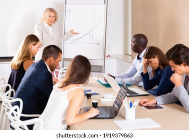Angry female boss reprehending colleagues on meeting in modern office