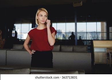 Angry female CEO dressed in formal wear calling with mobile phone to her colleagues which are late for a meeting, unmet businesswoman listening by cell telephone negative comment about last project