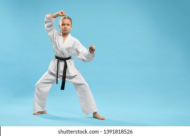 Angry female fighter in white kimono practising karate and jujitsu on blue isolated background. Sporty girl standing in stance and training in studio. Concept of martial arts and combat.
