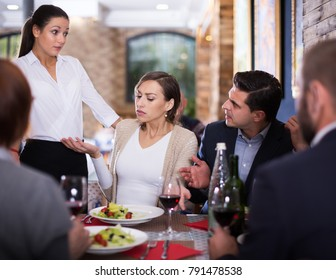 Angry female and male conflict with apologetic waitress about dish
