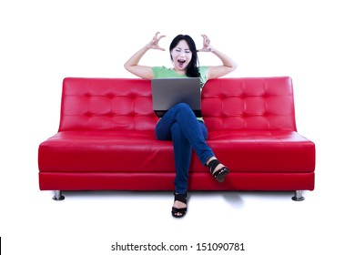 Angry female sitting on red sofa while looking at laptop on white background