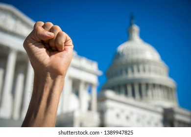 Angry fist of a protestor in the air under bright blue sky on a sunny day at Capitol Hill in Washington DC, USA