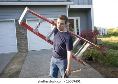 Angry, frowning man standing in front of house holding ladder and hammer. Horizontally framed photo.