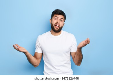 angry frustrated asian man with raised arms, expressing his disagreement. close up portrait, isolated blue background, studio shot. conflict, discussion