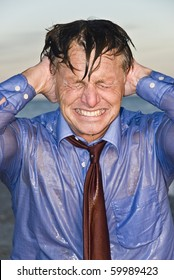 An angry and frustrated businessman soaked in water