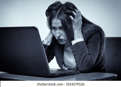 Angry and frustrated businesswoman watching her computer's screen