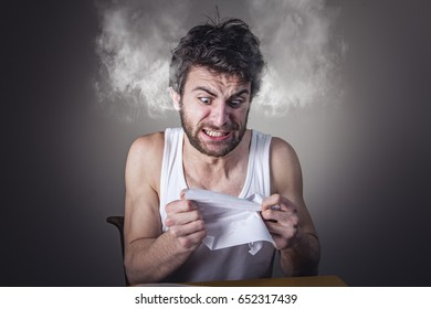 Angry frustrated man tearing apart is bills, smoke coming out of his head
