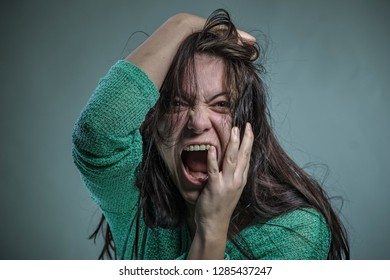 Angry frustrated woman screaming like crazy and pulling her hair