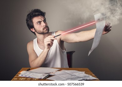 Angry frustrated young man burning paper bills with his laser pen