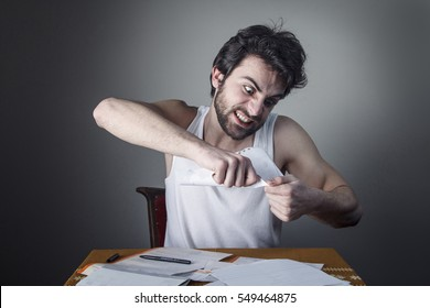 Angry frustrated young man tearing bills apart and throwing pieces all over the place