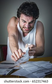 Angry and frustrated young man tearing his bills