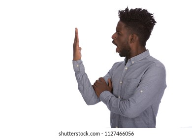 Angry furious African man shouting at his hand, isolated on a white background.